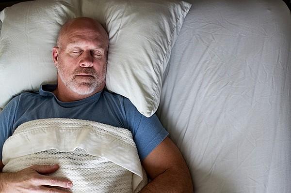 Мужчина спит на большой подушке